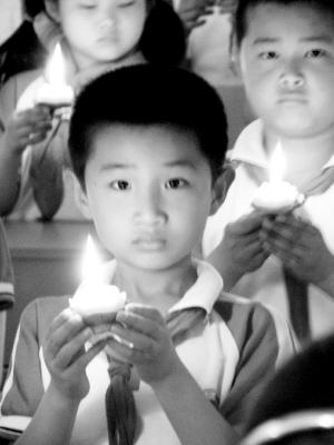 师生们手捧燃烧的蜡烛,神情肃穆.-安徽市场报社多媒体数字报刊